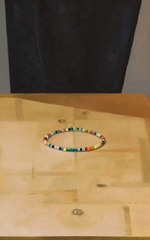 A still life painting of a string of beads on a wooden table with black cloth background