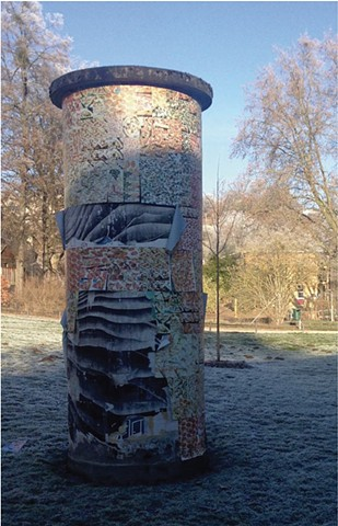 A Litfaßsäule in a park in the winter with faded and torn posters