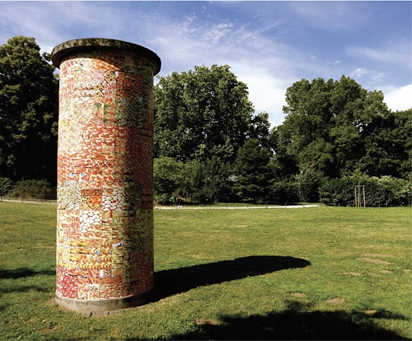 A Litfaßsäule in a park in the summer covered with photos of pizza