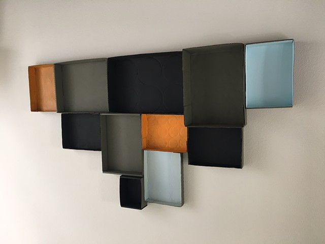 Painted cardboard boxes wall sculpture, blue, orange, black
