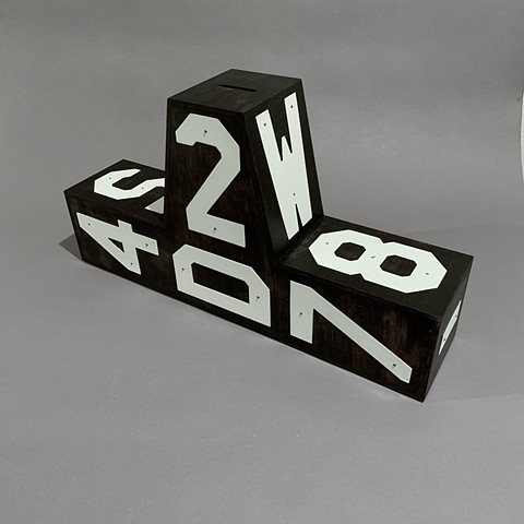 black and white wood sculpture with letters, passwords, piggy bank