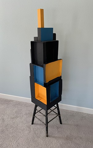 Painted cardboard boxes made into a tower atop an old stool