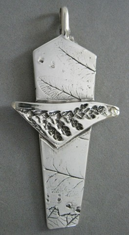 silver cross made by Nancy Denmark with impressions from nature