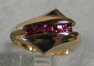 14K RING W/ CHANNEL OF RUBIES