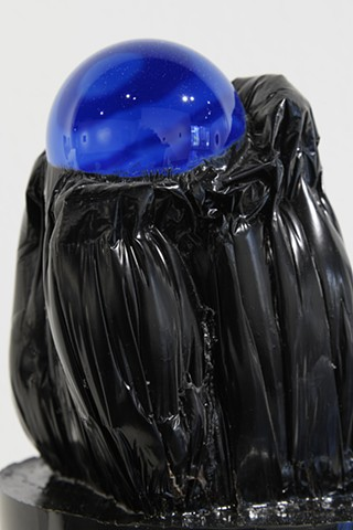 mixed media abstract sculpture with blue glass ball on top