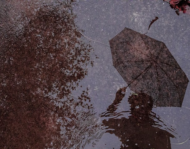 photo of reflection of figure holding umbrella