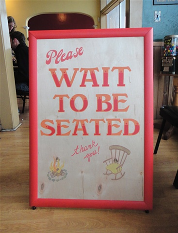 PLEASE WAIT TO BE SEATED sandwich board sign