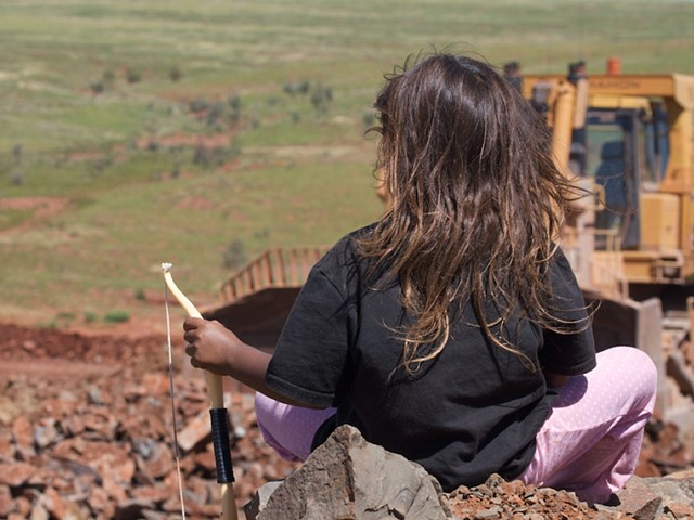 Image of girl looking on to Rio Tinto earthworks around bridge 13 after collapse.