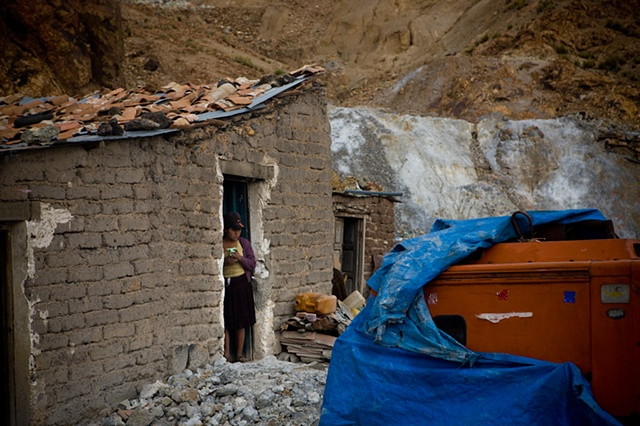A girl at the entrance of her house, which is situated next to the entrance of a mine. Entire families live guarding the entrance and the warehouses of the mines. A lot of looting with violence makes this a very dangerous job, specially for women (which a