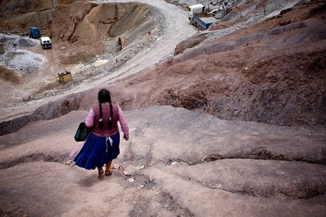 "A ""guardamina"" (woman who guards the entrance of the mines) walks down from the mine towards Potosi."