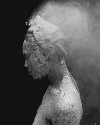 this is a photograph by los angeles based contemporary artist that is black and white of a figure that is covered in flour (not flowers). Esteban Schimpf made this artwork in California using a digital camera made by Fuji called the X100T. soon it will be
