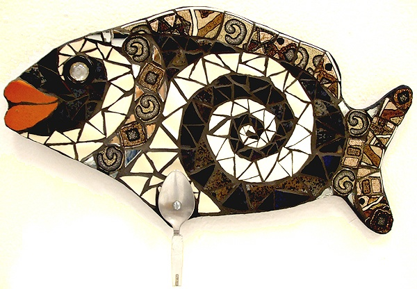 fish shaped mosaic wall art made from recycled materials, used dishes and stainless steel flatware. Has hook for hanging clothes, towels or utnesils.