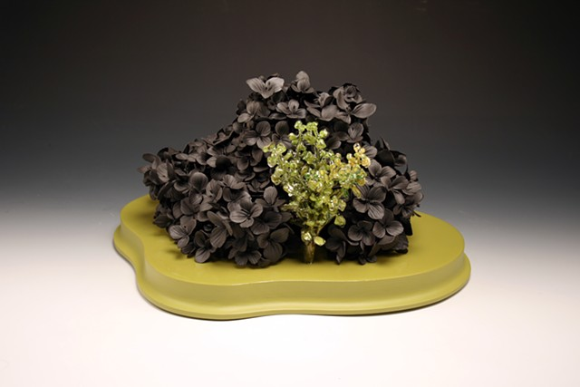 hand pinched black clay flower sculpture with resin dipped plastic flowers on a painted wood base
