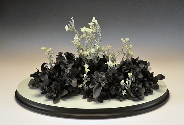 This is a hand built black clay and resin dipped flower tabletop sculpture on a painted wood base