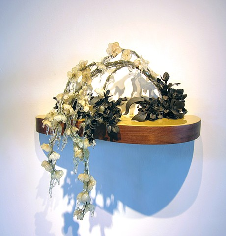This is a wall hung floral still life made of black clay flowers and resin dipped silk flowers on a vintage walnut base