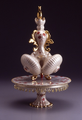 Red and gold porcelain sculpture with vintage decals on a porcelain and rhinestone stand