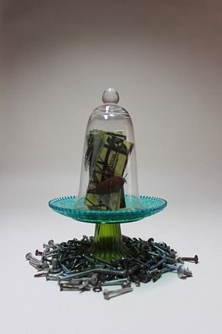 Book sculpture enclosed in bell jar.