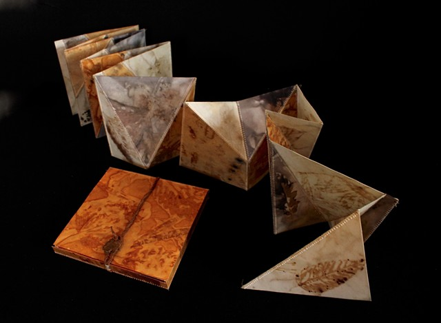 "Accordion book assembled from eco-printed pages using geometric pieces based on triangles and polygons.  Book folds flat (as a 6"" square) and can be pulled open/extended into multiple forms as a sculpture.  Nests into a box made from the same eco-printed"