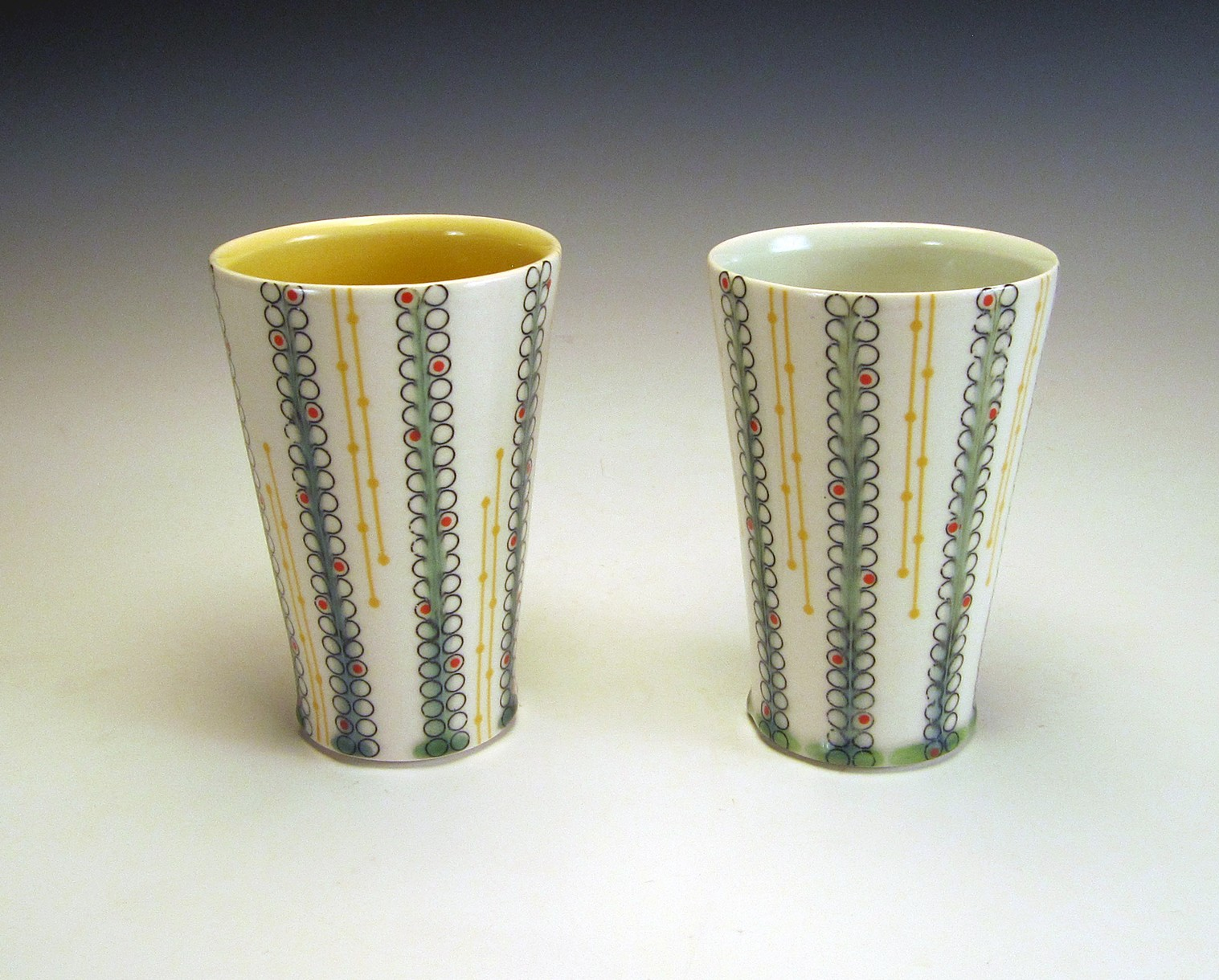 2 thrown porcelain tumblers with underglaze and overglaze decals